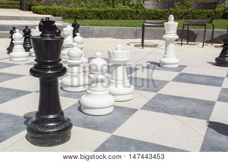 Street chessboard with chessmen and brown chairs in Europe