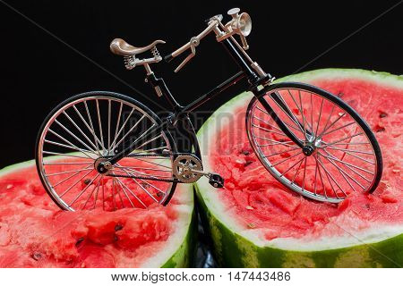 Paradox. Vintage bicycle standing on top of a large cut in half scarlet ripe watermelon