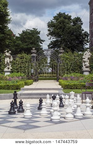 Black and white chessmen on the street chessboard with some green plants and monuments as background