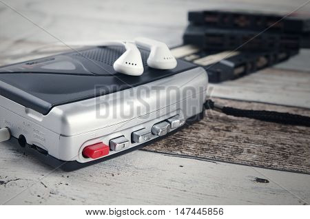 Old casette tape player and recorder with earphones on wooden background