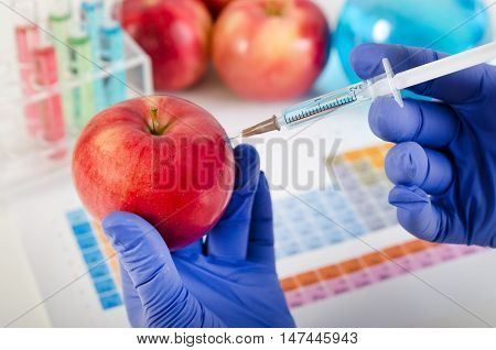 Analyst Injects Liquid Into Apple. Genetically Modified Food Concept.