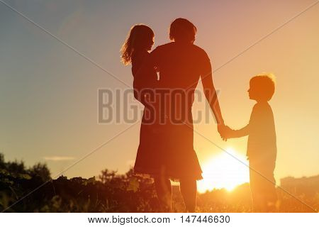 happy family concept - mother and two kids walking on sunset