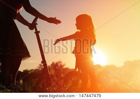 mother and little daughter riding scooter and bike at sunset sky