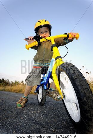 Baby boy riding on his first bike. Bike without pedals. Child learning to ride and balance on his two wheeler bike with no pedals.