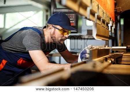 Portrait of worker near metalworking machine, industrial steel factory background.