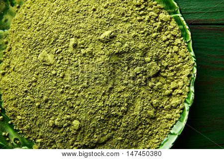 Matcha tea powder for japanese ceremony on green plate table