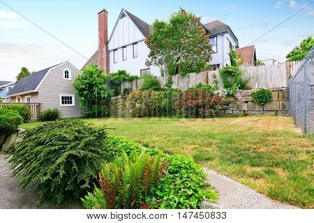 Back Yard House Exterior With Well Kept Garden Around.