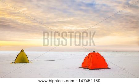 Bright tents camping of the expedition on the ice of the Northern territory. Wild adventure tours and trekking in the harsh winters of Northern nature. Courage and fortitude of traveler. North pole.