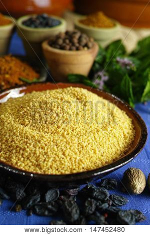 Organic couscous and different spices in traditional eastern clay bowls ingredients for salad