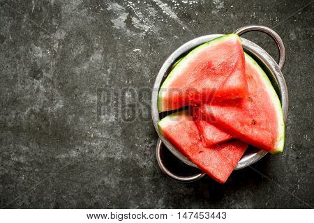 Watermelon chunks in a metal bowl. On the stone table.