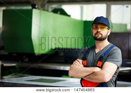 Portrait of worker in overalls with crossed arms, industrial steel factory background.