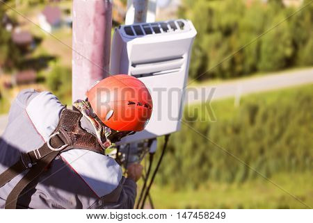 worker on the telecommunications tower with a wrench. installation of telecommunication equipments. tower technician installs transmitter to the telecommunications tower