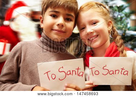 Couple of kids, boy and girl, standing by Christmas tree holding their letters with wishes  and smiling happily to camera, as santa claus sneaking in background