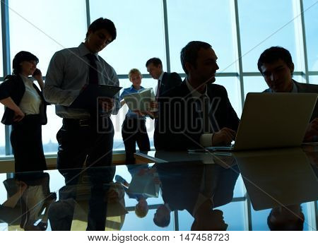 Image of six busy businesspeople against the window lit from behind