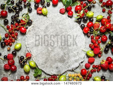 Frame of wild berries with free place for text. On the stone table.