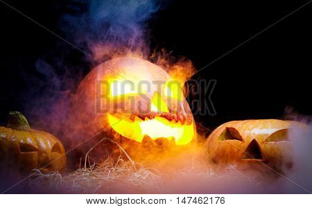 Jack O Lantern blazing and smoking on straw among two other pumpkins that are unlit against black background