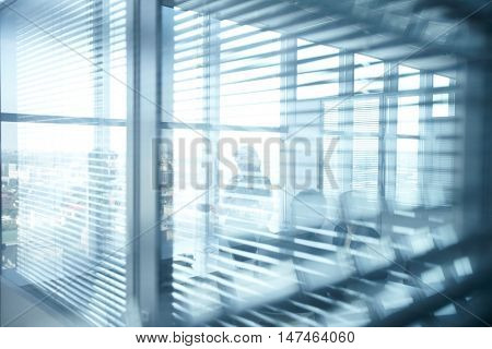Silhouettes of people working in light office behind the blinds