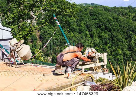 Sochi, Russia - MAY 22, 2016: Mason worker tiler making floor in a new buildings of the SKYPARK AJ Hackett Sochi, in the Sochi National Park, a scenic location Ahshtyrskaya gorge