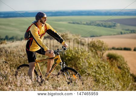 Young man cycling on a rural road through green summer meadow during sunset