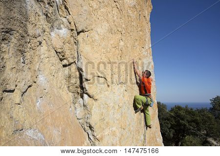 Climber rappelling from the summit of a rock spire after a challenging ascent. poster