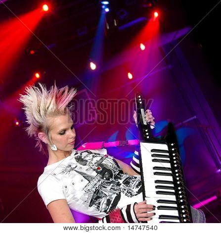 Beautiful punk rocker playing key-tar during concert
