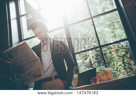 Reading latest news. Low angle view of confident young man reading fresh newspaper while leaning at the window sill in office or cafe