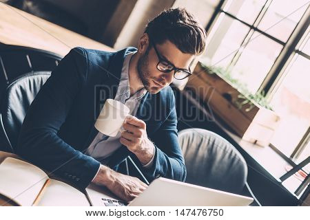 Enjoying fresh coffee while working. Confident young man in smart casual wear working on laptop and holding coffee cup while sitting at his working place in office
