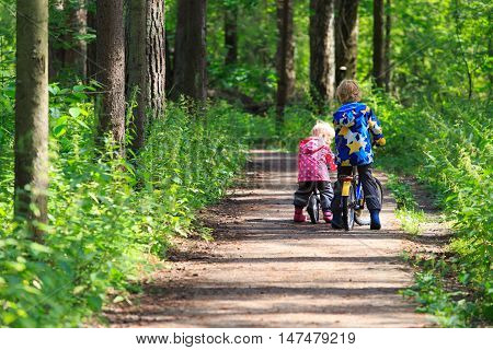 kids sport - little boy and girl riding bikes in green forest