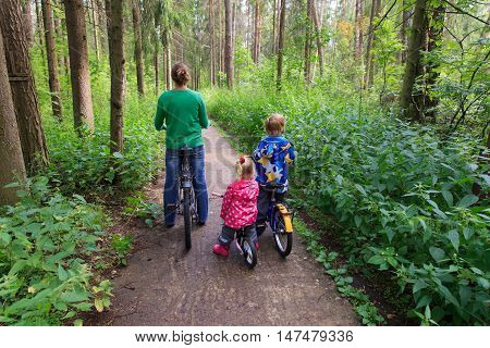 mother with little son and daughter riding bikes in summer forest