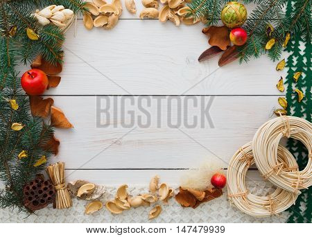 Christmas decoration handmade frame concept background, top view with copy space on white wood table surface. Creative diy craft hobby, tools and trinkets for christmas ornaments, garland and balls.