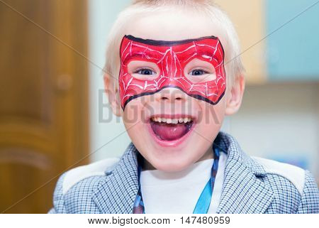 Excited caucasian boy with a spiderman mask on his face smiles at camera.