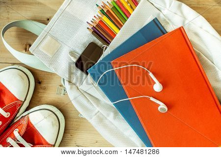 back to school concept - school kids bag with pencils cellphone earphones and college material ready with shoes on wooden background