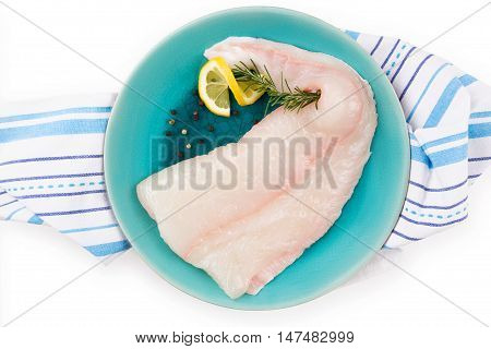 Raw halibut fillet on plate. Culinary seafood cooking.