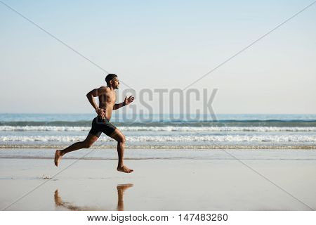 Powerful Black Man Running Barefoot By The Sea