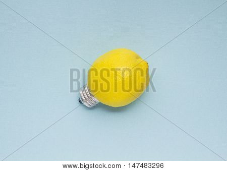 Creative concept photo of a lemon with a bulb on blue background.