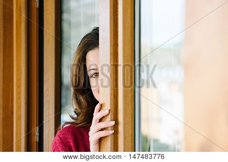 Playful Woman Peeking Through Home Window