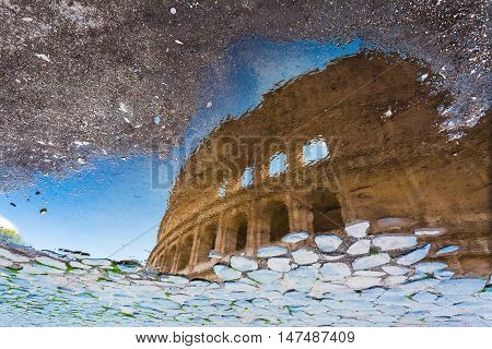 ROME, ITALY - September  12, 2016: Colosseum in Rome, Italy (reflection in the puddle on the road of cobblestones after rain)