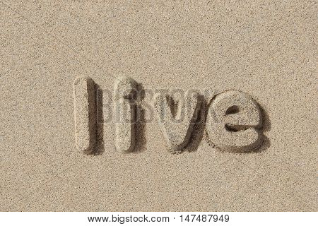 Live written in sand letters. Very simple and graphic.