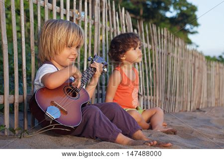 Little happy boy have fun play music on Hawaiian guitar ukulele for small baby girl enjoying sunset ocean beach. Children healthy lifestyle. Travel family activity on tropical island summer holiday