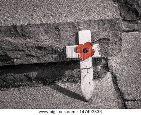FLANDERS FIELDS, BELGIUM - MAY 12, 2016: A small wooden cross with a poppy attached leans against a concrete step in a cemetery in western Belgium. There are nearly 800 cemeteries holding the remains of the casualties of the First World War.