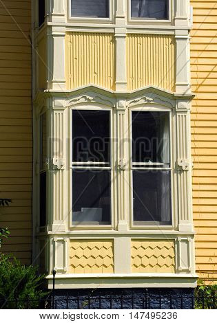 Beautifuly trimmed double windows on Victorian home are painted in cream and yellow.