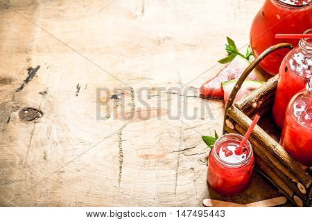 Watermelon juice with pulp. On wooden background.