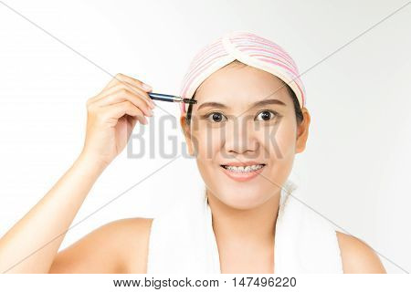 portrait of young beautiful woman with brush for make-up. Eyelbrows zone