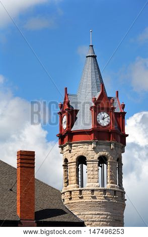 Soughton Clock Tower is framed by a blue sky and clouds. Historic Victorian architecture stands near downtown.