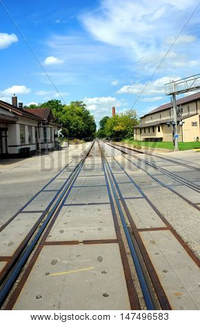 Historic train depot sits besides railroad tracks in Stoughton Wisconsin. Tracks disappear into distance.