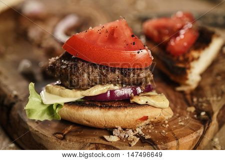 quarter fresh homemade burger with marble beef, cheese and vegetables on olive board, shallow focus
