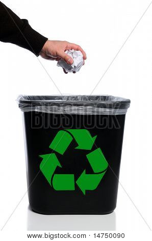 Man's hand placing paper in trash can with recycle symbol