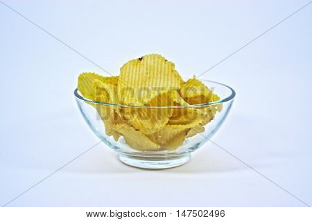 Crinkle cut potato chips in a clear bowl on a white background