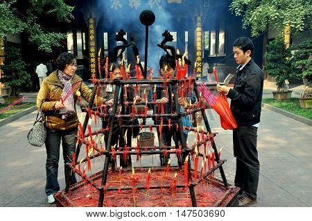 Xindu China - Ocrober 28 2010: Faithful Buddhist visitors light incense sticks from a hexagonal cast-iron holder ablaze with candles at the centuries-old Bao Guang Temple