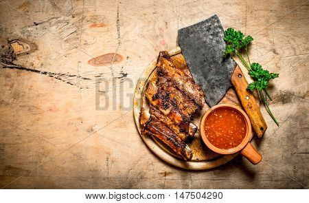 Barbecued ribs with tomato sauce and a carving hatchet. On wooden background.